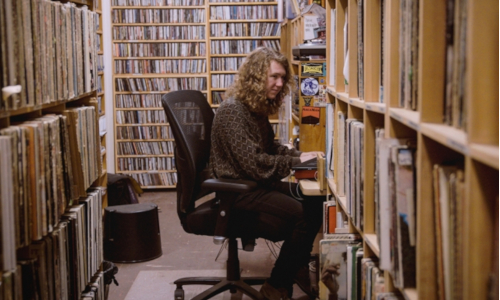 Trevor Henderson in the record library at WMBR
